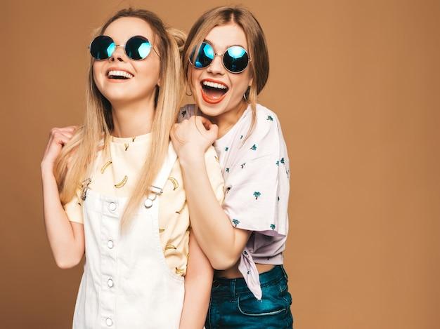 Due giovani belle ragazze bionde sorridenti dei pantaloni a vita bassa in vestiti variopinti della maglietta di estate alla moda. donne spensierate sexy che posano sul fondo beige in occhiali da sole rotondi. modelli positivi che si divertono