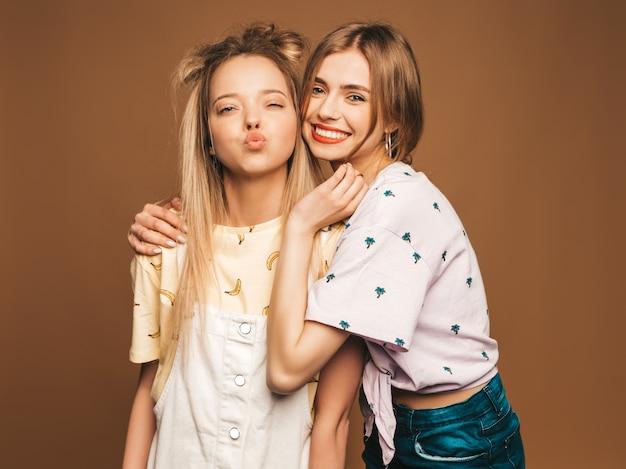 Due giovani belle ragazze bionde sorridenti dei pantaloni a vita bassa in vestiti variopinti della maglietta di estate alla moda. donne spensierate sexy che posano sul fondo beige. modelli positivi che danno bacio