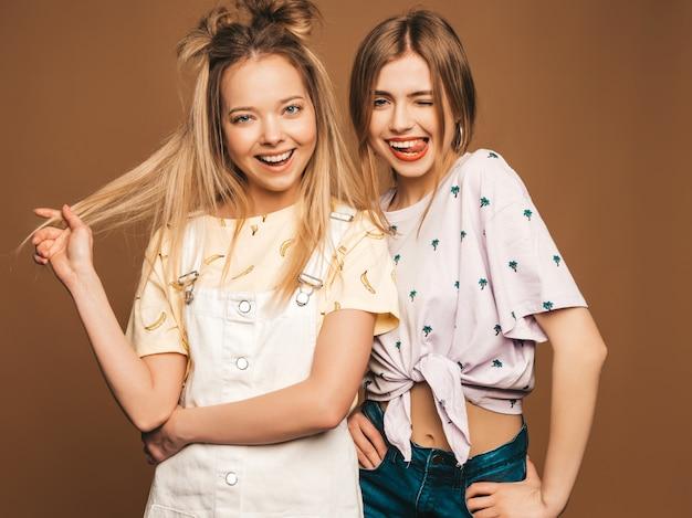Due giovani belle ragazze bionde sorridenti dei pantaloni a vita bassa in vestiti variopinti della maglietta di estate alla moda. donne spensierate sexy che posano sul fondo beige. modelli positivi che si divertono