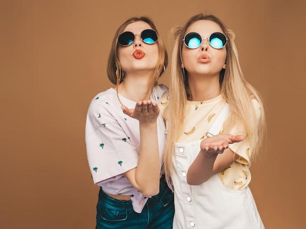 Due giovani belle ragazze bionde sorridenti dei pantaloni a vita bassa in vestiti variopinti della maglietta di estate alla moda. donne spensierate sexy che posano vicino alla parete beige in occhiali da sole rotondi. modelli positivi che danno un bacio d'aria
