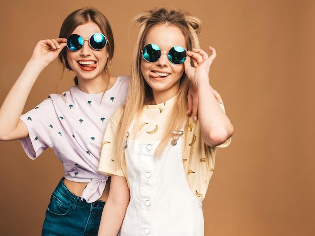 Due giovani belle ragazze bionde sorridenti dei pantaloni a vita bassa in vestiti variopinti della maglietta di estate alla moda. donne spensierate sexy che posano vicino alla parete beige in occhiali da sole rotondi. modelli positivi che mostrano la lingua