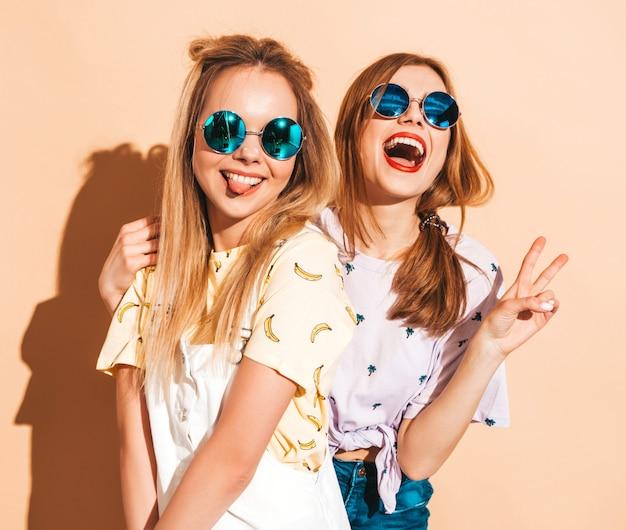 Due giovani belle ragazze bionde sorridenti dei pantaloni a vita bassa in vestiti variopinti della maglietta di estate alla moda. donne spensierate sexy che posano vicino alla parete beige in occhiali da sole rotondi. mostra il segno di pace
