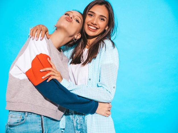 Due giovani belle ragazze bionde sorridenti dei pantaloni a vita bassa in vestiti variopinti della maglietta di estate alla moda. donne spensierate sexy che posano vicino alla parete blu. i modelli positivi si divertono e fanno la faccia di anatra