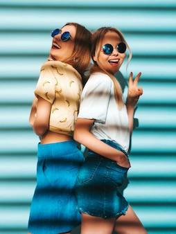 Due giovani belle ragazze bionde sorridenti dei pantaloni a vita bassa in vestiti variopinti della maglietta di estate alla moda. donne spensierate sexy che posano vicino alla parete blu in occhiali da sole rotondi. modelli positivi che mostrano il segno di pace