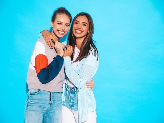 Due giovani belle ragazze bionde sorridenti dei pantaloni a vita bassa in vestiti variopinti della maglietta di estate alla moda. donne spensierate sexy che posano vicino alla parete blu. modelli positivi che si divertono