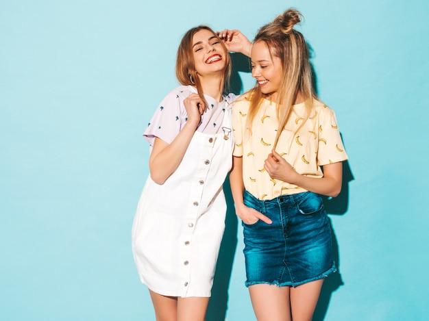Due giovani belle ragazze bionde sorridenti dei pantaloni a vita bassa in vestiti variopinti della maglietta di estate alla moda. e abbracci