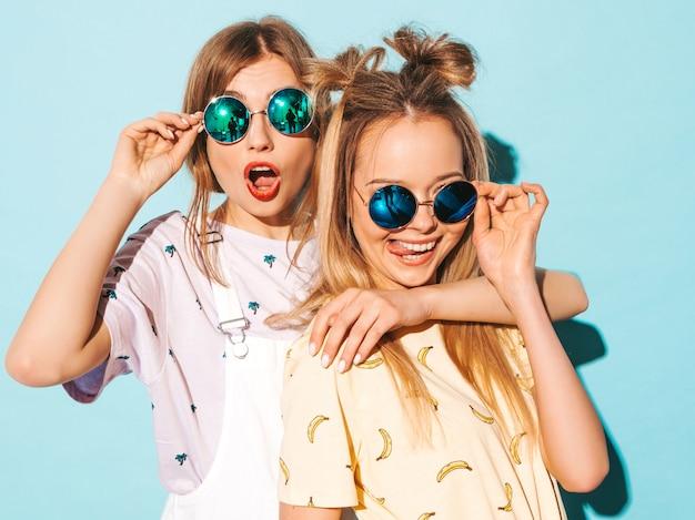 Due giovani belle ragazze bionde sorridenti dei pantaloni a vita bassa in vestiti variopinti della maglietta di estate alla moda. e mostrando la lingua