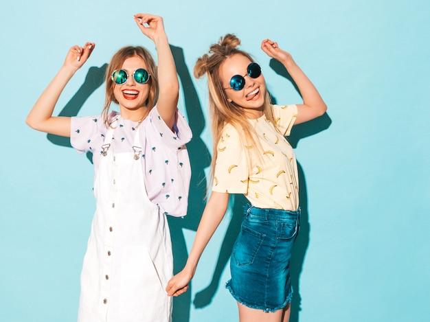 Due giovani belle ragazze bionde sorridenti dei pantaloni a vita bassa in vestiti variopinti della maglietta di estate alla moda.