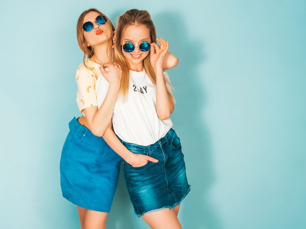 Due giovani belle ragazze bionde sorridenti dei pantaloni a vita bassa in vestiti variopinti di estate d'avanguardia.