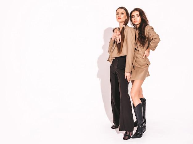 Due giovani belle ragazze castane in abiti alla moda simili di bella estate alla moda