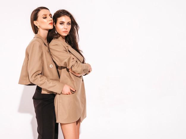 Due giovani belle ragazze castane in bei vestiti alla moda estate vestito