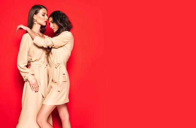 Due giovani belle ragazze castane in bei vestiti estivi alla moda