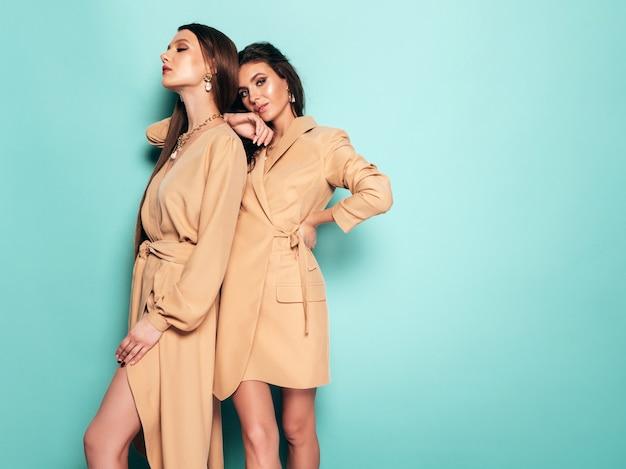 Due giovani belle ragazze castane in bei vestiti estivi d'avanguardia donne spensierate sexy che posano vicino alla parete blu in studio abbraccio femminile