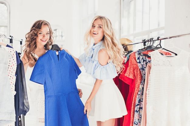 Due giovani belle ragazze che guardano i vestiti e provano mentre scelgono al negozio