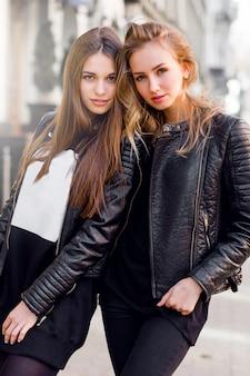 Due giovani belle ragazze che propongono insieme all'aperto. umore urbano di stile di vita. sfondo centro città. le migliori amiche che indossano abiti casual neri per l'autunno.