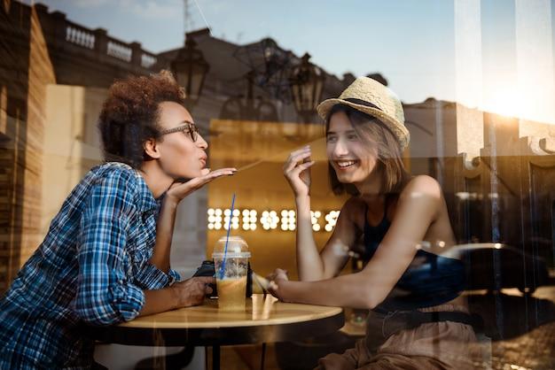 Due giovani belle ragazze che sorridono, parlando, riposando nella caffetteria. sparato dall'esterno.