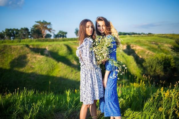 Due giovani belle ragazze europee in un campo di fiori di campo
