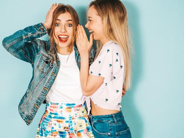 Due giovani belle ragazze sorridenti bionde dei pantaloni a vita bassa in abbigliamento casual di estate alla moda.