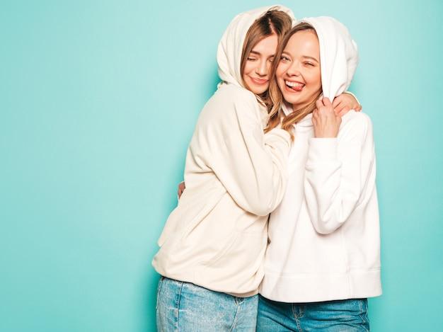 Due giovani belle ragazze sorridenti bionde dei pantaloni a vita bassa in vestiti alla moda con cappuccio dell'estate. donne spensierate sexy che posano vicino alla parete blu. i modelli alla moda e positivi mostrano gli occhiali da sole con segno della lingua