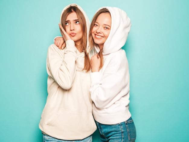 Due giovani belle ragazze sorridenti bionde dei pantaloni a vita bassa in vestiti alla moda con cappuccio dell'estate. donne spensierate sexy che posano vicino alla parete blu. modelli alla moda e positivi che si divertono