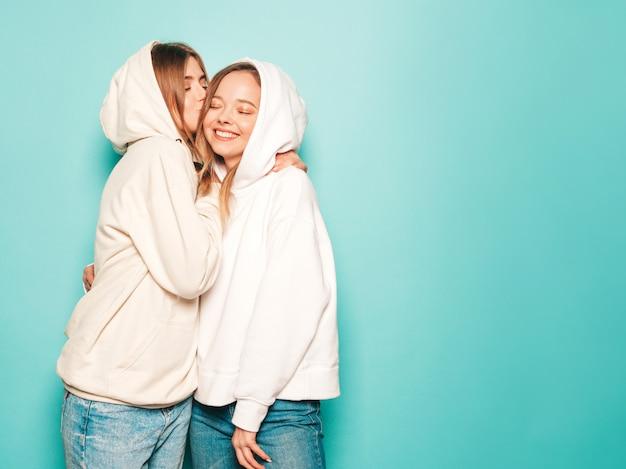 Due giovani belle ragazze sorridenti bionde dei pantaloni a vita bassa in vestiti alla moda con cappuccio dell'estate. donne spensierate sexy che posano vicino alla parete blu. modello che bacia la sua amica in testa