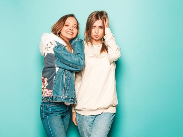 Due giovani belle ragazze sorridenti dei pantaloni a vita bassa castana in vestiti d'avanguardia della giacca con cappuccio e dei jeans dell'estate. donne spensierate sexy che posano vicino alla parete blu. modelli alla moda e positivi che si divertono