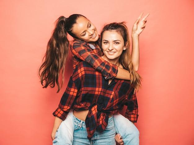 Due giovani belle ragazze sorridenti dei pantaloni a vita bassa del brunette in vestiti a quadretti simili d'avanguardia della camicia e dei jeans donne spensierate sexy che posano vicino alla parete blu in studio divertimento dei modelli positivi