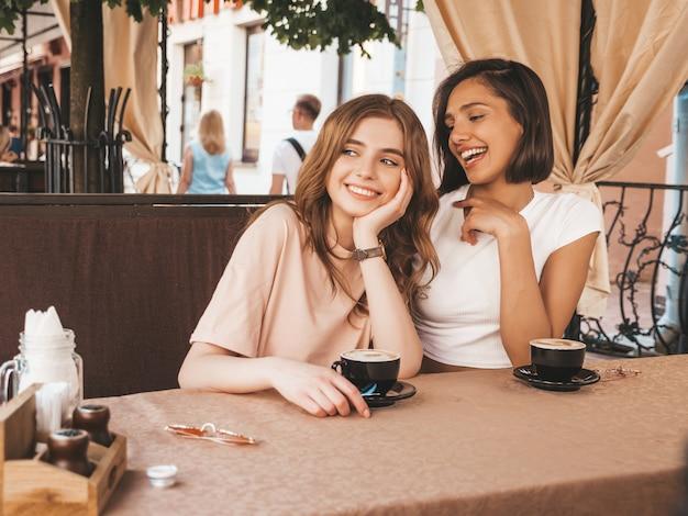 Due giovani belle ragazze sorridenti dei pantaloni a vita bassa in abbigliamento casual estivo alla moda. donne spensierate che chiacchierano nel caffè della terrazza della veranda e bevono caffè. modelli positivi che si divertono e comunicano