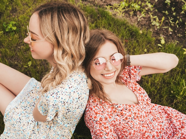 Due giovani belle ragazze sorridenti dei pantaloni a vita bassa in prendisole estive d'avanguardia donne spensierate sexy che si trovano sull'erba verde in occhiali da sole divertimento dei modelli positivi vista superiore