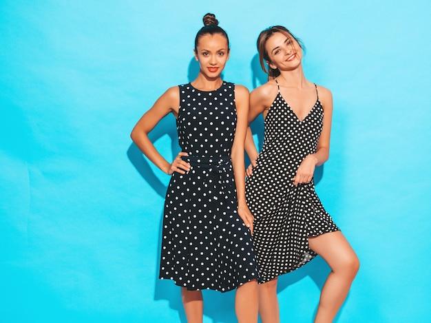Due giovani belle ragazze sorridenti dei pantaloni a vita bassa in vestiti alla moda di estate a pois. donne spensierate sexy che posano vicino alla parete blu avere divertimento e abbracciare. le modelle mostrano buone relazioni. femmina con labbra rosse