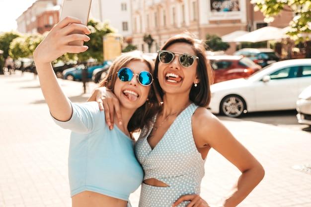 Due giovani belle ragazze sorridenti dei pantaloni a vita bassa in vestiti d'avanguardia di estate donne spensierate sexy che posano sui precedenti della via in occhiali da sole. scattano selfie selfie su smartphone al tramonto