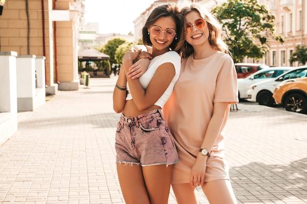 Due giovani belle ragazze sorridenti dei pantaloni a vita bassa in vestiti d'avanguardia di estate donne spensierate sexy che posano sul fondo della via in occhiali da sole. modelle positive che si divertono e impazziscono
