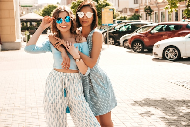 Due giovani belle ragazze sorridenti dei pantaloni a vita bassa in vestiti d'avanguardia di estate donne spensierate sexy che posano sul fondo della via in occhiali da sole. modelli positivi che si divertono e si abbracciano