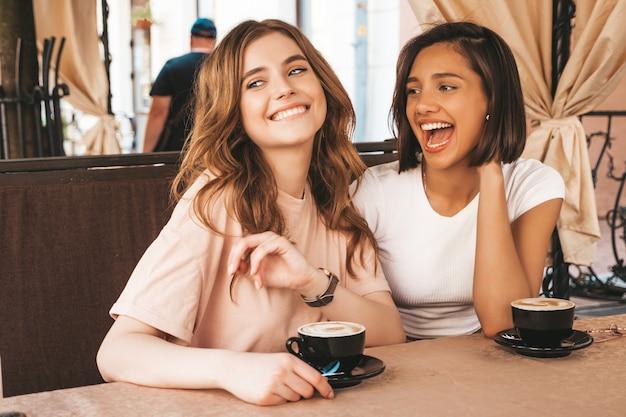 Due giovani belle ragazze sorridenti dei pantaloni a vita bassa in vestiti estivi d'avanguardia donne libere che chiacchierano nel caffè della terrazza della veranda e che bevono caffè modelli modulari divertendosi e comunicando