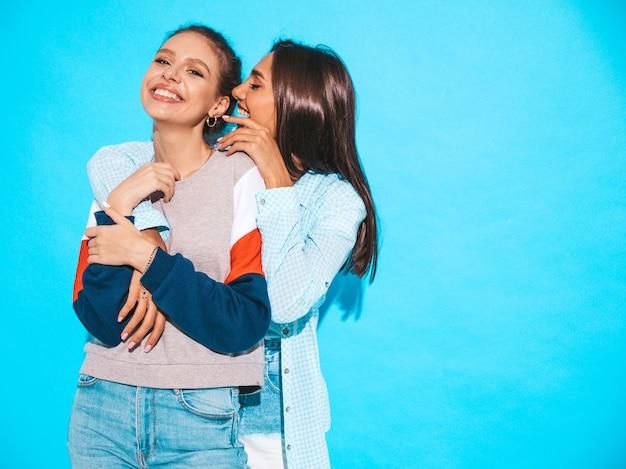 Due giovani belle ragazze sorridenti hipster in abbigliamento casual estivo alla moda. le donne sexy condividono segreti, gossip.isolato sul blu. emozioni facciali sorprese