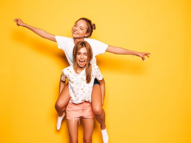 Due giovani belle ragazze sorridenti hipster in abiti estivi alla moda. donne spensierate sexy che posano vicino alla parete gialla. modello che si siede sulla schiena dell'amica e che solleva le mani