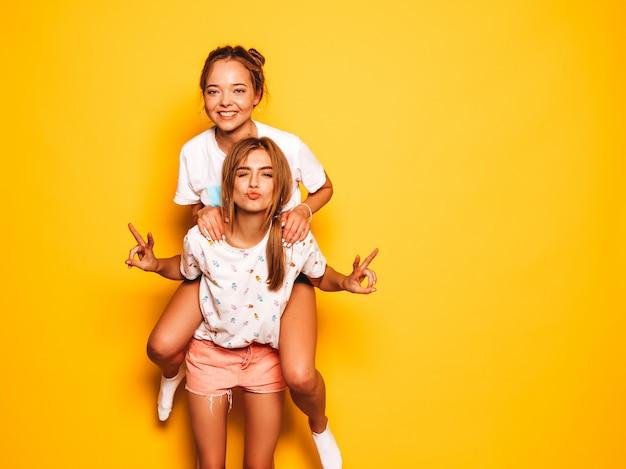 Due giovani belle ragazze sorridenti hipster in abiti estivi alla moda. donne spensierate sexy che posano vicino alla parete gialla. modello che si siede sulla schiena della sua amica e mostra il segno di pace