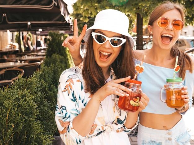 Due giovani belle ragazze sorridenti hipster in abiti estivi alla moda e cappello panama.