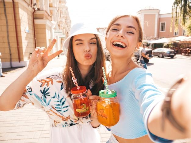 Due giovani belle ragazze sorridenti hipster in abiti estivi alla moda