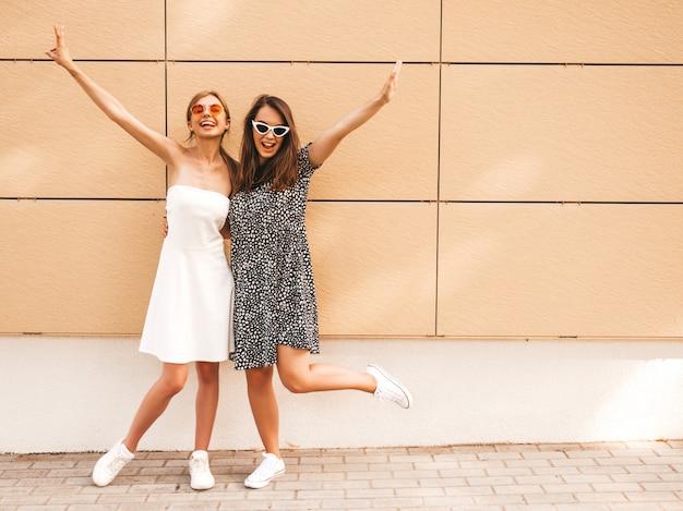 Due giovani belle ragazze sorridenti hipster in abiti estivi alla moda.