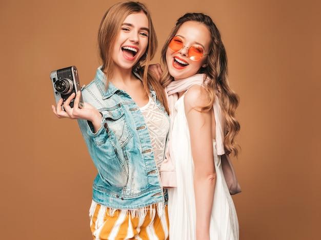 Due giovani belle ragazze sorridenti in abiti casual e occhiali da sole alla moda estate. posa sexy spensierata delle donne. scattare foto con fotocamera retrò