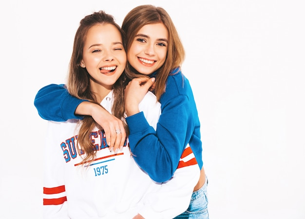 Due giovani belle ragazze sorridenti in abiti estivi alla moda. donne sexy spensierate. modelli positivi che ammiccano e mostrano la lingua