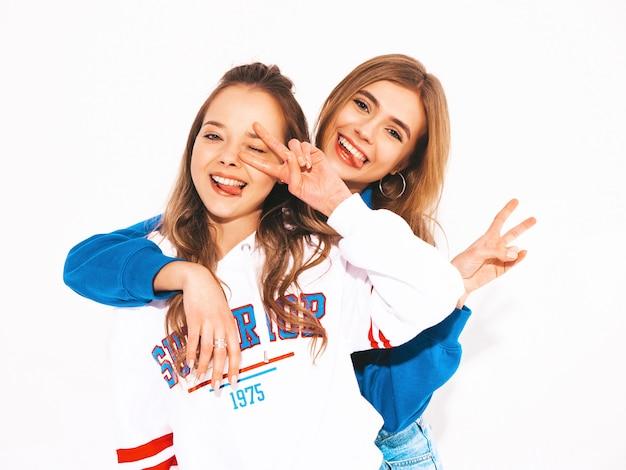 Due giovani belle ragazze sorridenti in abiti estivi alla moda. donne sexy spensierate. modelli positivi che mostrano il segno di pace