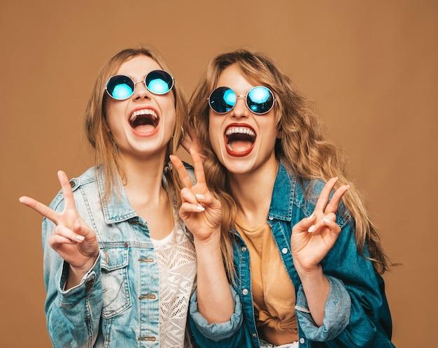 Due giovani belle ragazze sorridenti in abiti estivi alla moda e occhiali da sole. posa sexy spensierata delle donne. modelle urlanti positive