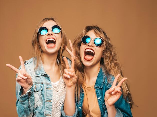 Due giovani belle ragazze sorridenti in abiti jeans alla moda estate e occhiali da sole. posa sexy spensierata delle donne. modelli di grido positivi che mostrano il segno di pace