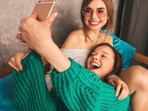 Due giovani belle ragazze sorridenti splendide in abiti estivi alla moda. donne spensierate sexy che posano nell'interno e che prendono selfie. modelli positivi che si divertono con lo smartphone.
