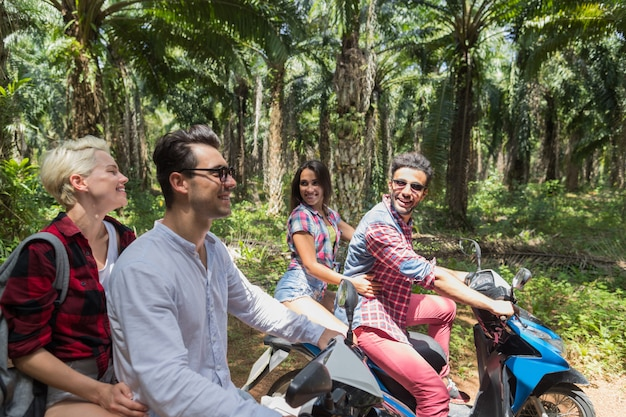 Due giovani coppie che fanno il viaggio in scooter felice persone viaggiano