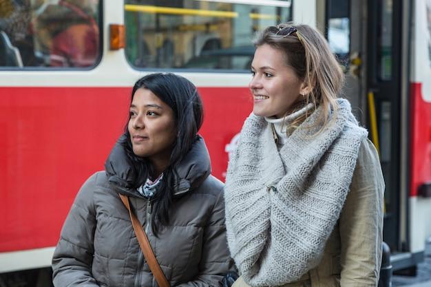 Due giovani donne alla fermata del tram