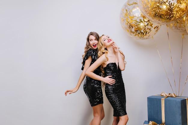 Due giovani donne alla moda attraenti in abiti neri di lusso che celebrano la festa. divertirsi, sguardo elegante, sorridere, emozioni vere. grande regalo, palloncini dorati, orpelli.