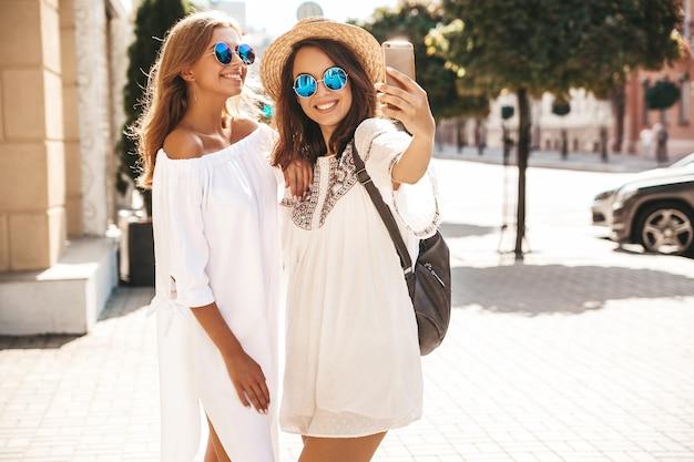 Due giovani donne alla moda hippy donne castane e bionde modellano nel giorno soleggiato dell'estate in vestiti bianchi dei pantaloni a vita bassa che prendono le foto del selfie per i media sociali sul telefono. wome positivo